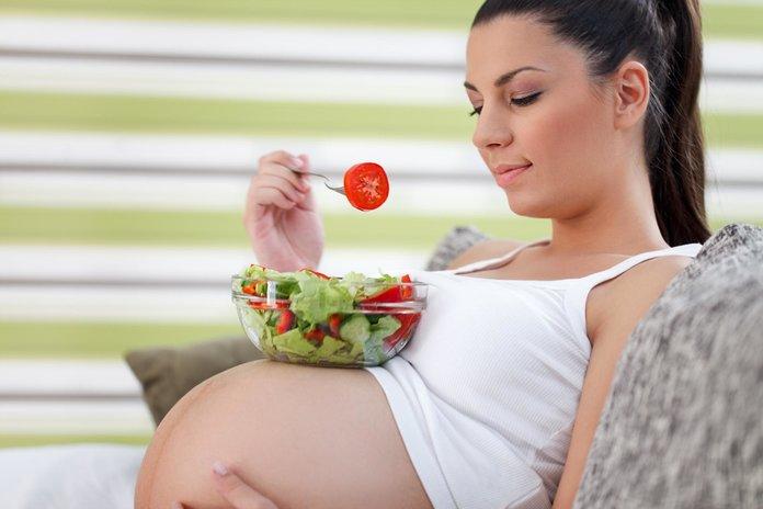 Беременная ест салат с пекинской капустой