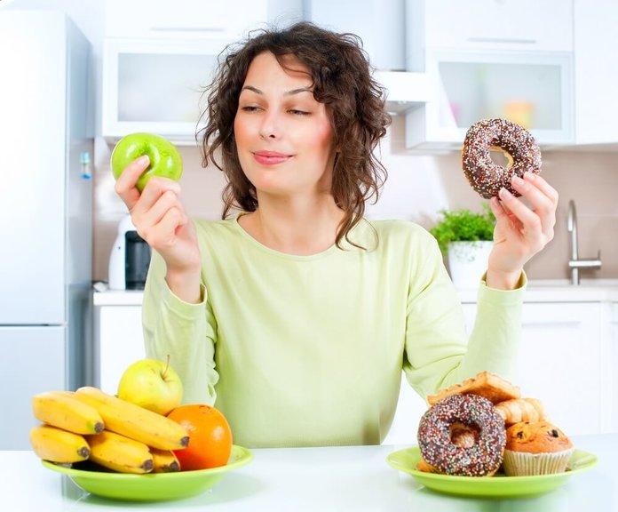 Девушка делает выбор между фруктами и сладостями