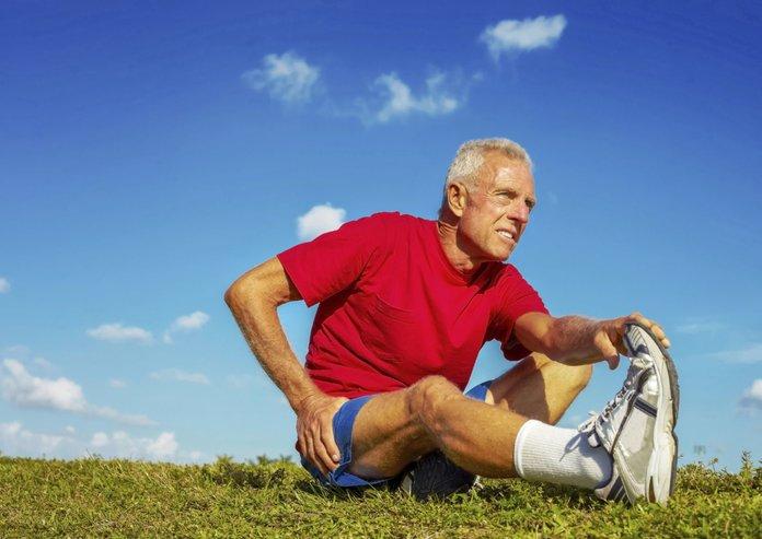 Пожилой мужчина делает упражнение на растяжку