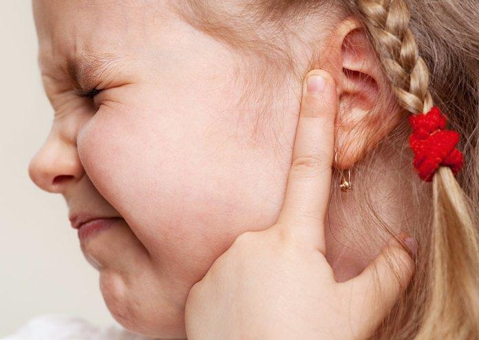 Ребенок прижимает ушко от боли