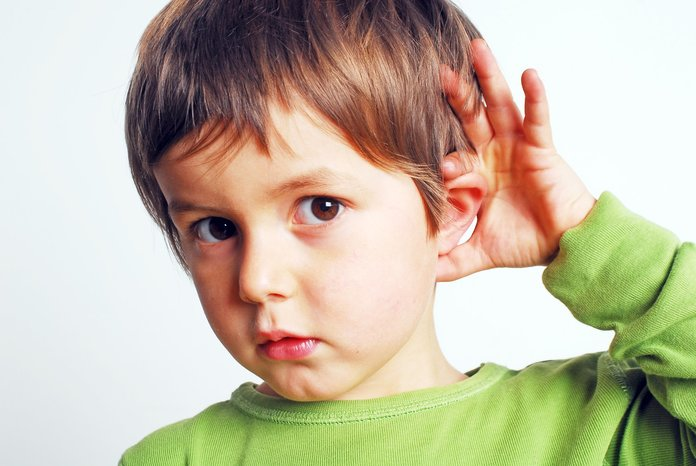 Мальчик держится за ухо