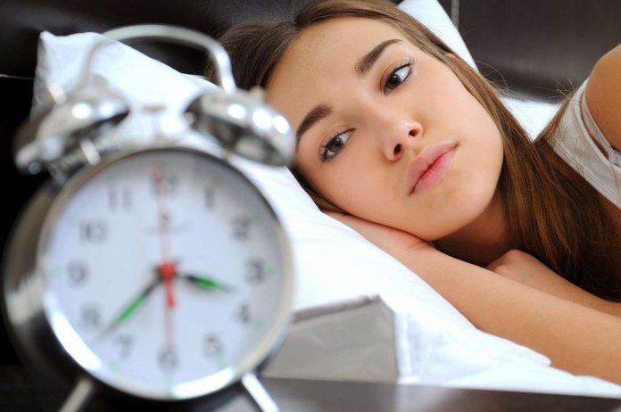 Девушка с бессоницей смотрит на часы