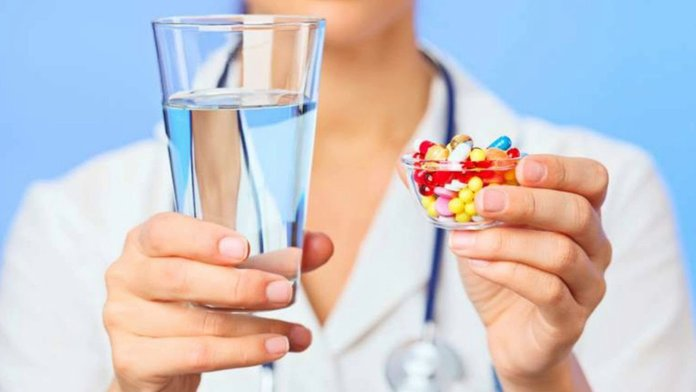 Доктор с таблетками и стаканом воды