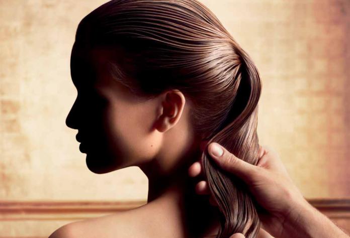 Девушка обрабатывает волосы кедровым маслом