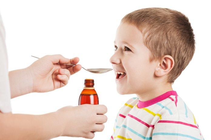 Мальчик принимает сироп с тимьяном против простуды
