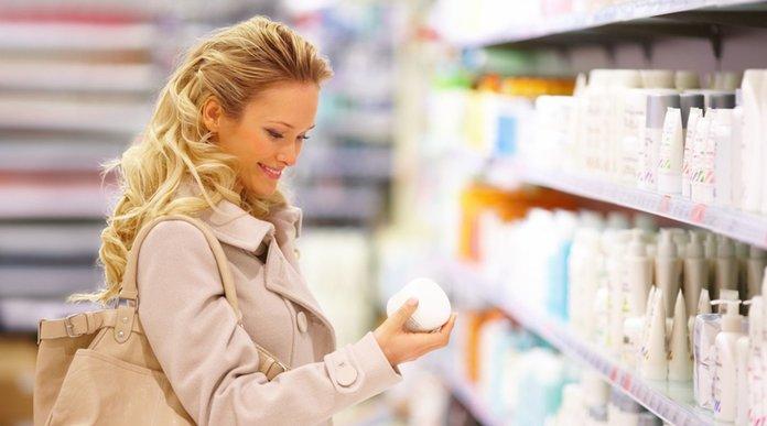 Девушка выбирает лекарство в аптеке