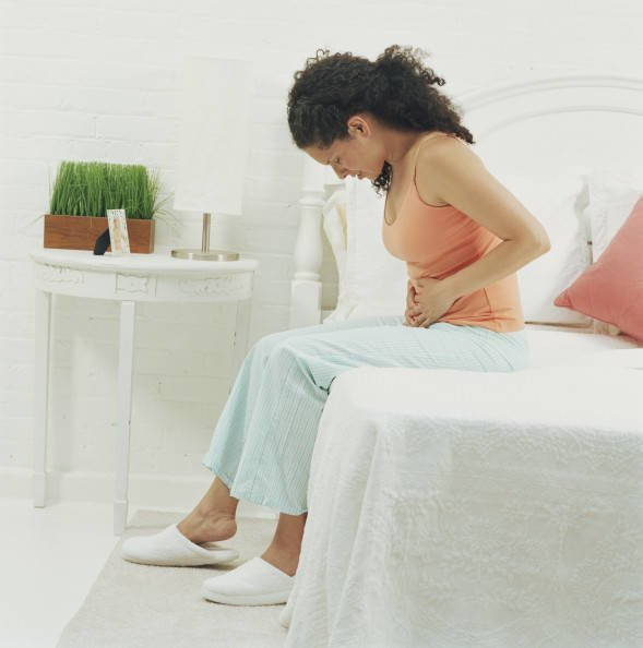 Woman sitting on bed holding stomach, head bowed